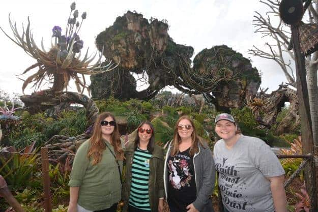 A group of people standing in front of a tree posing for the camera