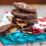A rolo cake cookie split in half in front of a stack of chocolate cookies.