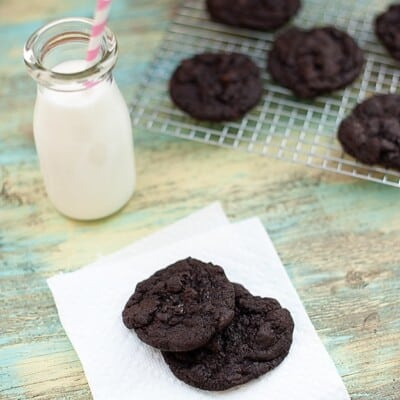 Two chocolate cookies on a napkin in front of a jar of milk