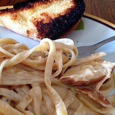 Alfredo chicken and garlic bread on a plate.