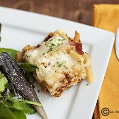 Ziti on a small square plate with salad