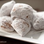 Beignets stacked on a paper napkin.
