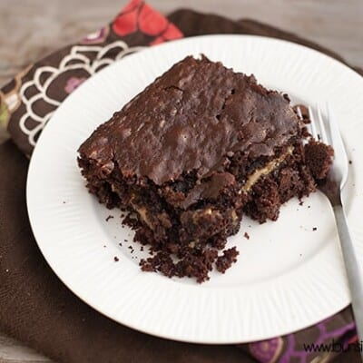 A gooey chocolate cake on a white plate with a fork