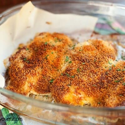 A cheesy crusted chicken breast in a glass baking dish