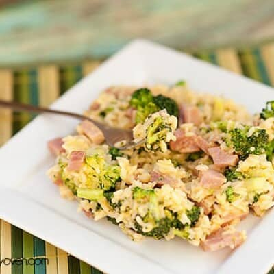 A plate of broccoli and diced ham with a fork in it.