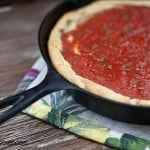 A cast-iron skillet with pizza dough and tomato sauce on it.