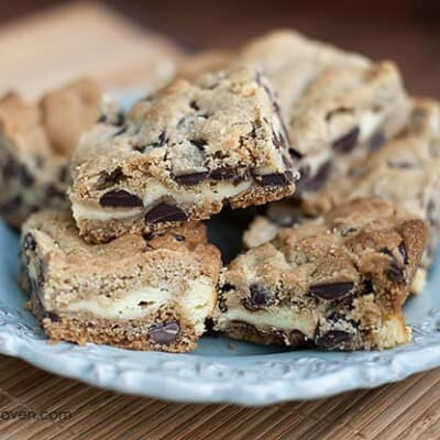 A bunch of chocolate chip cheesecake cookie bars on a plate.