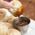 A person dipping a cinnamon biscuit ball.