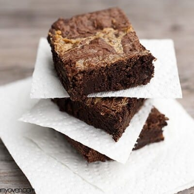 Three stacked up brownies with paper napkins in between them