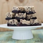 A stack of cookie dough brownies on a cake stand