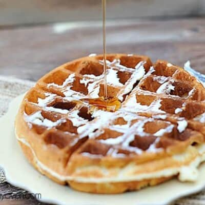 Syrup drizzling on top of a waffle.