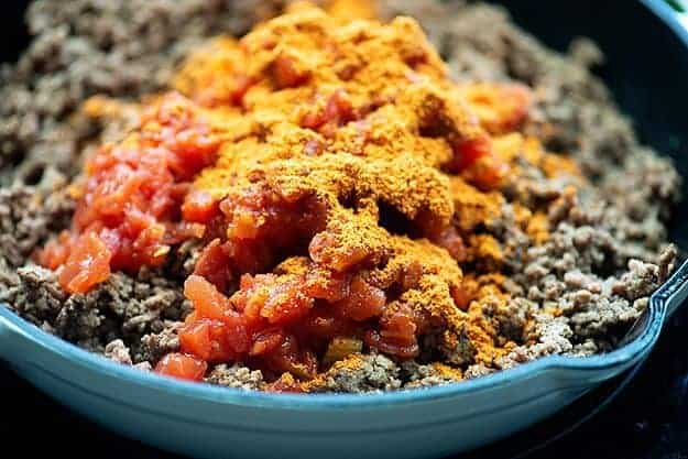 taco meat with tomatoes and chiles in white pan