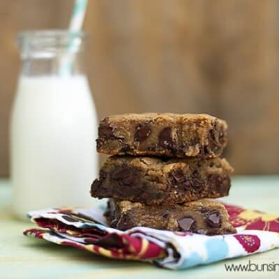 Three chocolate chip cookie bars stacked on a folded cloth napkin