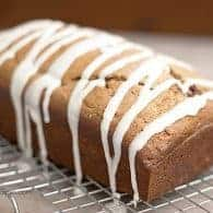 A loaf of maple cinnamon quick bread topped with icing.