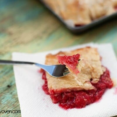 A fork resting on top of a serving of raspberry slab pie.