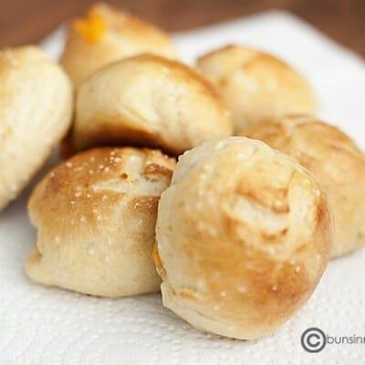 A close up of pretzel rolls on a paper napkin.