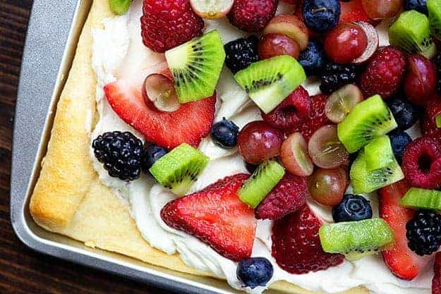 cream cheese fruit pizza on baking sheet