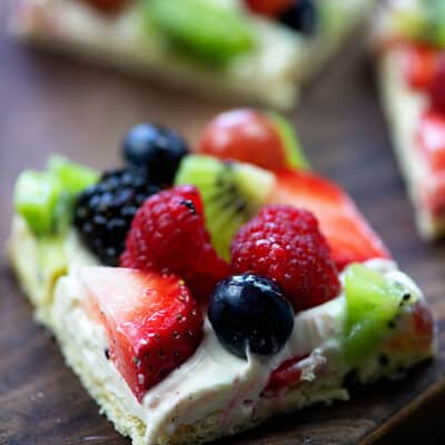 A square piece of fruit pizza on a wooden table.