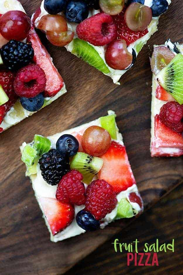 Several square fruit pizzas on a wooden table.