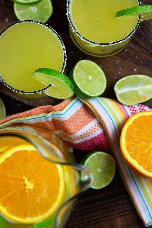 A glass of margarita next to a bunch of sliced oranges.