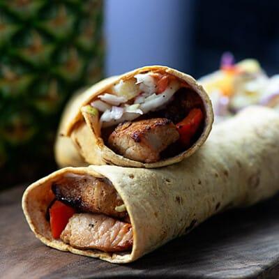 grilled pork sandwich wraps on cutting board