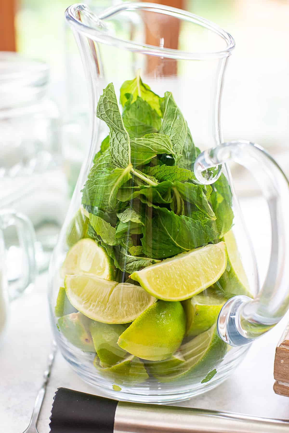 limes and mint in glass mitcher.