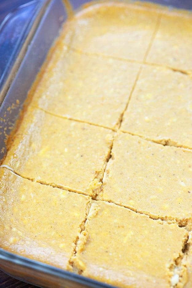 A baking sheet of cheesecake bars cut into many squares.