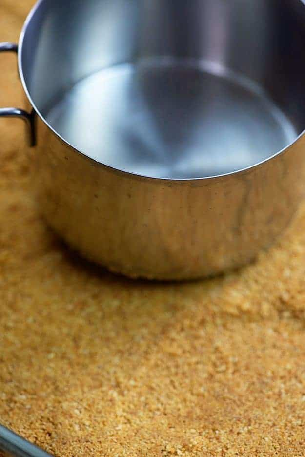 pressing graham cracker crust into pan with measuring cup