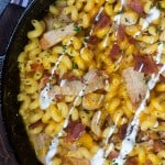 Bacon rand macaroni and cheese pasta in a cast-iron skillet.