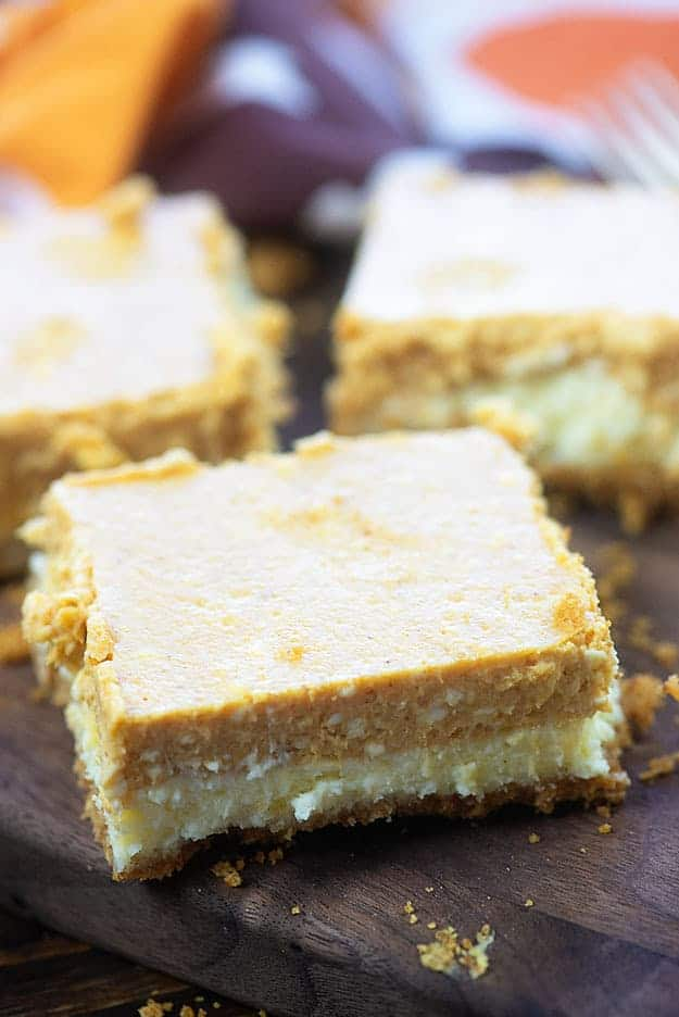 A pumpkin cheesecake square on top of a cutting board.