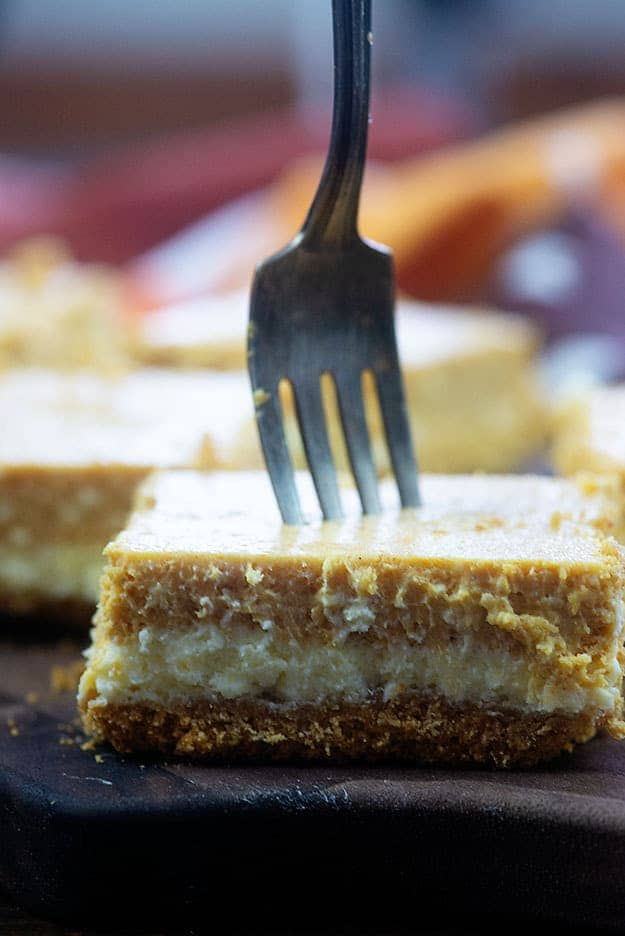 A square of cheesecake with a fork stabbing through it.