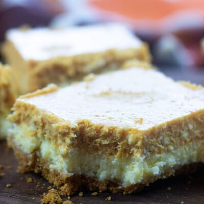 A square of pumpkin cheesecake with a bite taken out of it.
