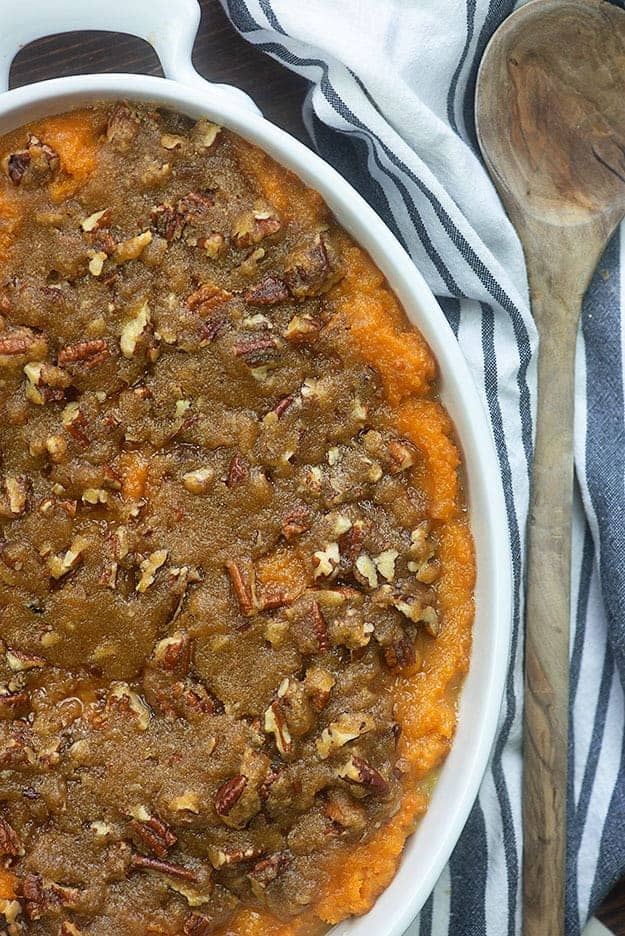 Sweet potato casserole in a white pan on a cloth napkin.