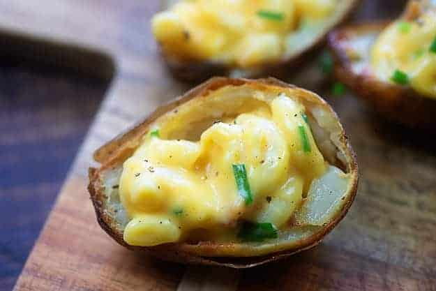 potato skins filled with macaroni and cheese on cutting board