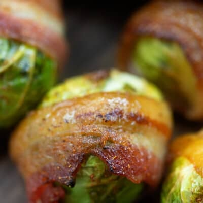Brussel sprouts wrapped in bacon on a cutting board.