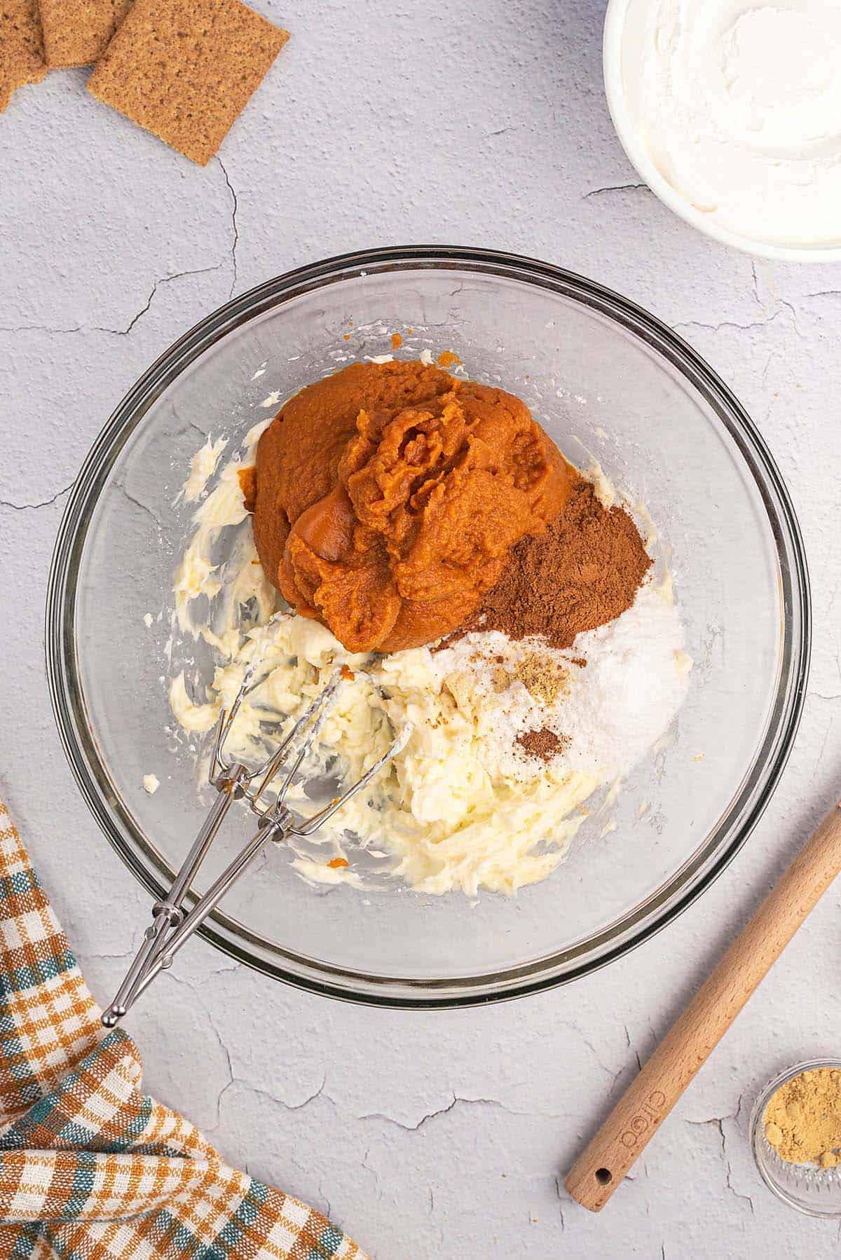 ingredients for pumpkin dip in glass bowl.