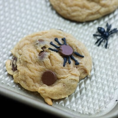 Chocolate chip cookie and a plastic spider on a baking sheet.