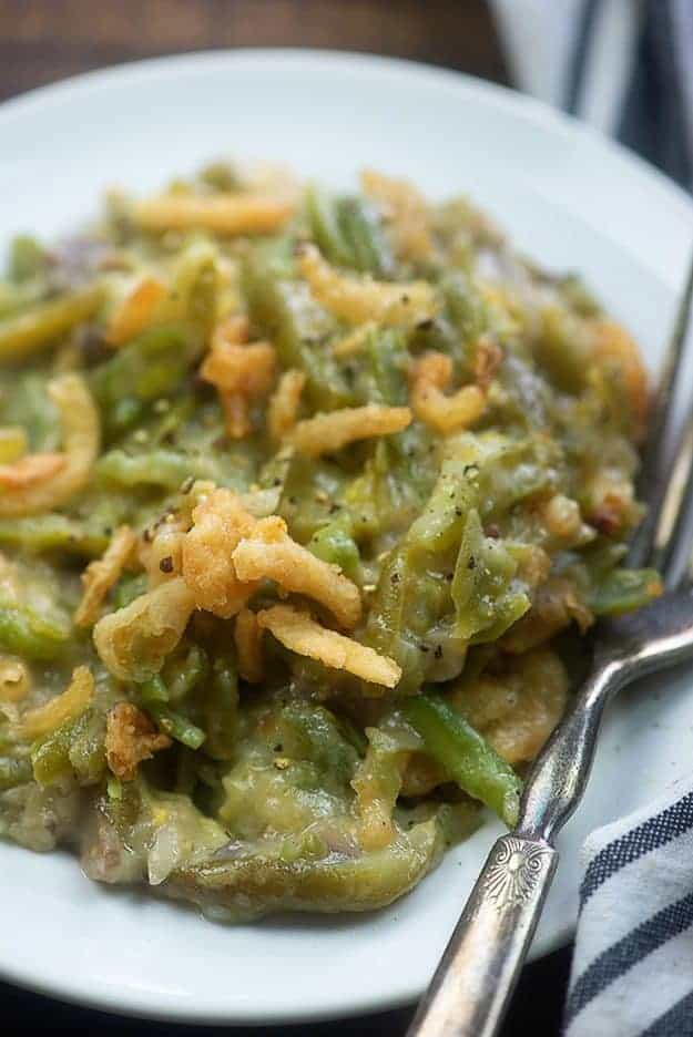 Green bean casserole and a fork on a white plate.