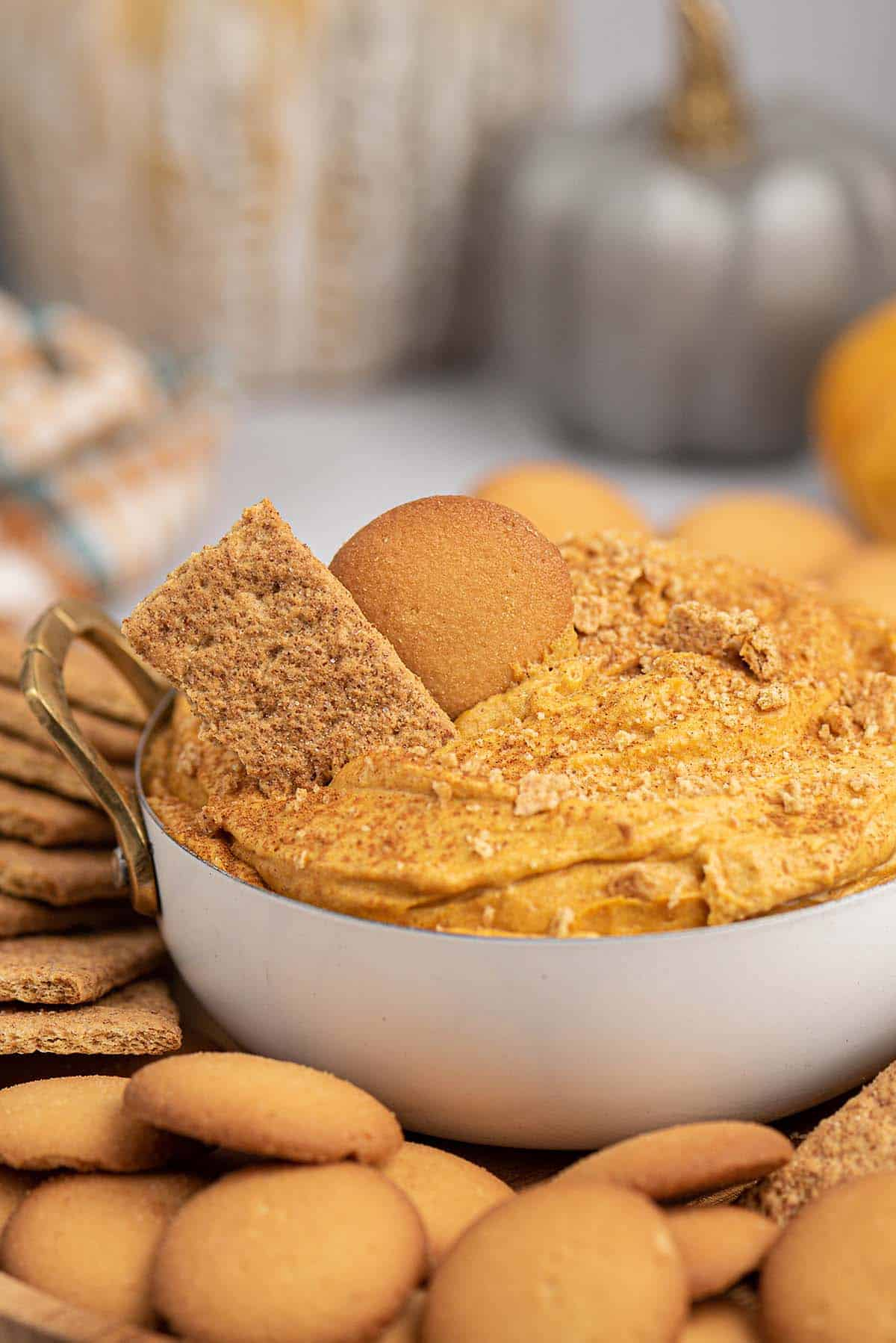 bowl of pumpkin pie dip surrounded by cookies and crackers.