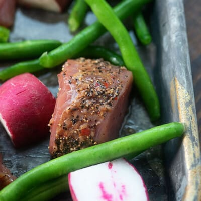A close up a chunk of pork, radishes, and green beans on a sheet pan.