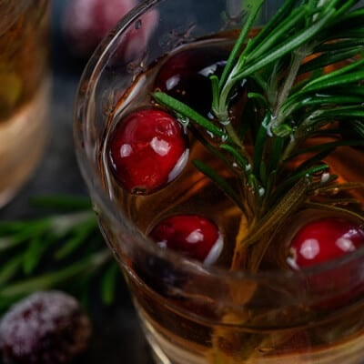 Close up of a glass of sangria with cherries floating on top.