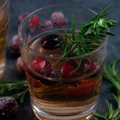 A glass of sangria on a table with rosemary.