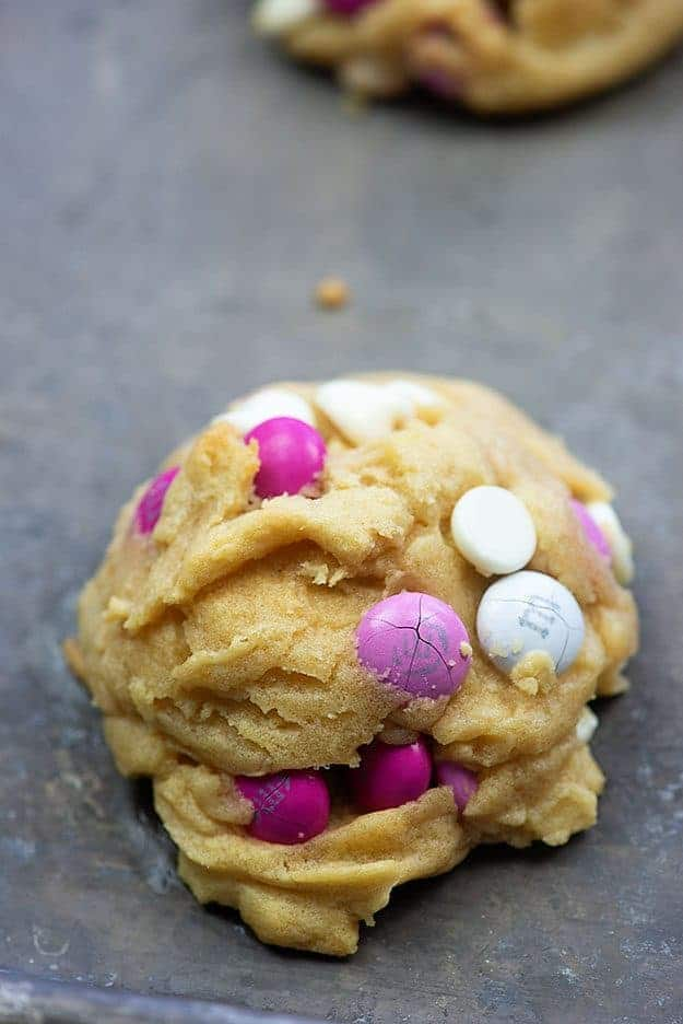 A close up of white chocolate chip cookie with Valentine M&M\'s.