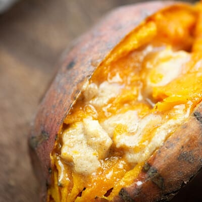 A close up of food, with Sweet potato with melted butter in the middle.