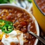 A bowl of chili next to a pot.