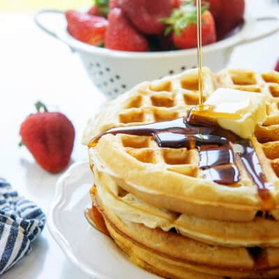 stack of Belgian waffles on white plate.