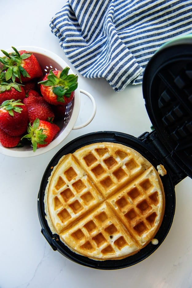 waffle in waffle iron next to strawberries.