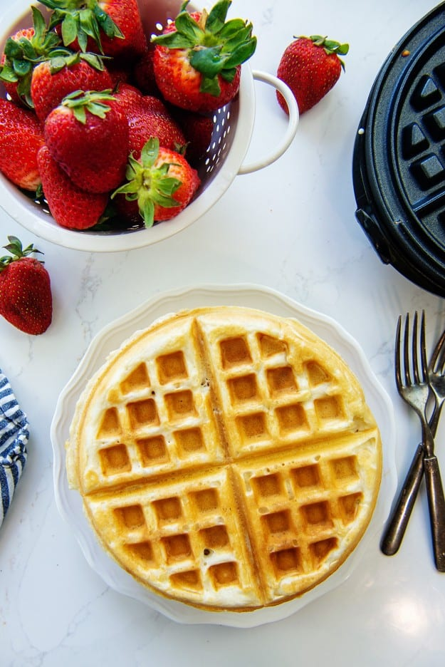 waffles on plate next to strawberries.