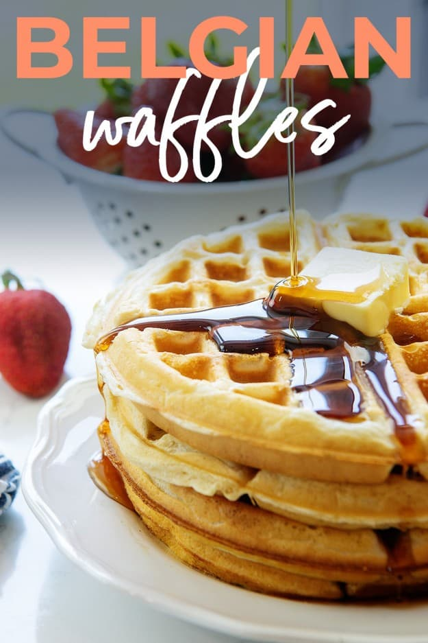 Belgian waffles on white plate with syrup and butter.