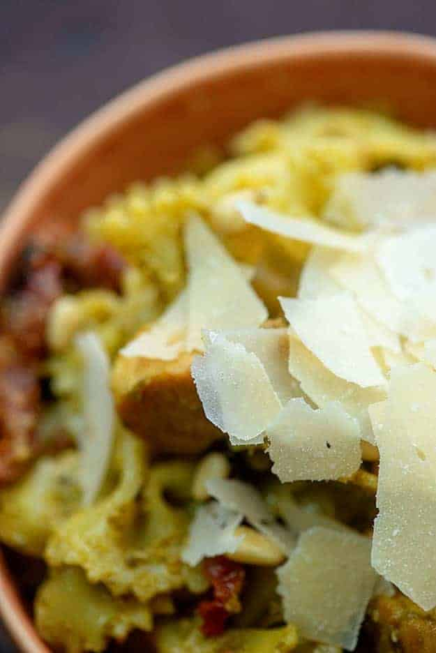 A close up of a plate of cheese flakes on top of a bowl of pasta.